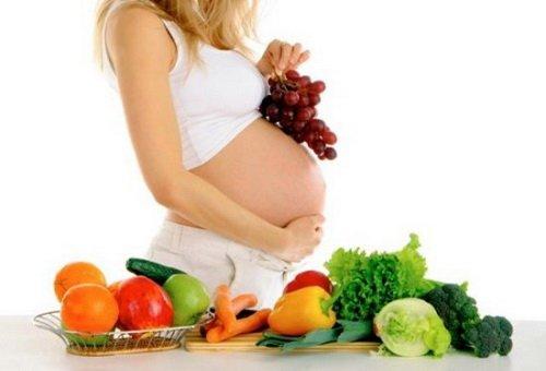 беременная с фруктами и овощами